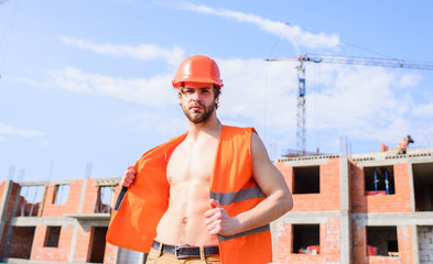 Builder sexy muscular torso macho dream of every woman. Sexy macho foreman. Guy protective helmet stand in front of building made out of red bricks. Builder orange vest helmet work construction site