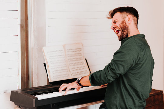 Young man playing electric piano at home