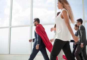 businessman superhero and his business team walking in office
