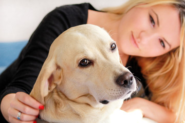Woman with dog is resting in bed at home, relaxing in bedroom. Girl is petting with her dog. Portrait of cute yellow labrador retriever and her owner, enjoying on blue bed, posing in front of camera.