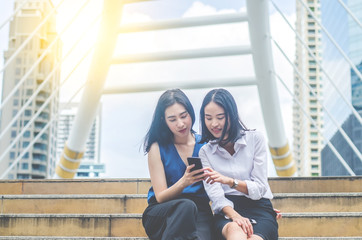 Two beautiful young women sitting on the stairs and enjoy  watching videos on a smartphone
