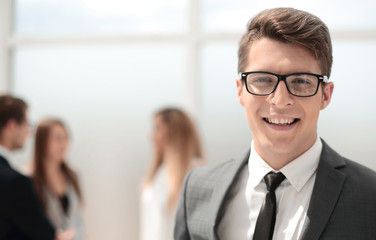 smiling young businessman on blurred office background.