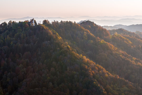 Church on top of rolling forest hills in autumn colors illuminated with soft sunlight early morning