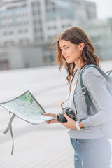 beautiful female traveler with photo camera and map in city