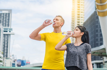 Young sporty couple drinking fresh water after running for their health with happy and relax mood, sport in the city,