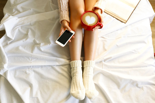 Lazy afternoon concept. Close up shot of woman sitting in bed, reading book, holding red cup of cappuccino coffee with heart shaped latte art foam & blank screen mobile phone. Background, copy space.