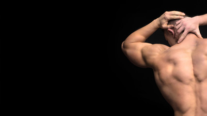 The back view of torso of attractive male body builder on dark background