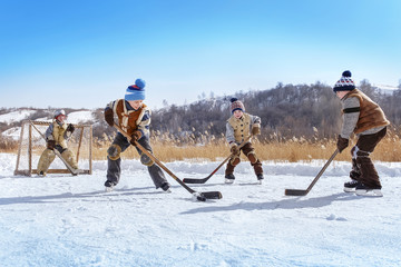 Boys play hockey on a frozen lake