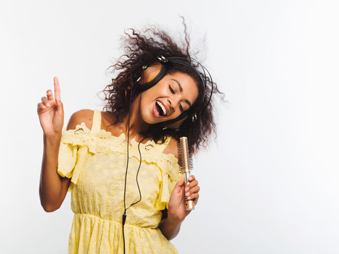 Young pretty african american woman in yellow dress singing and dancing with hair dryer instead microphone at white wall. Black girl having fun isolated on background.