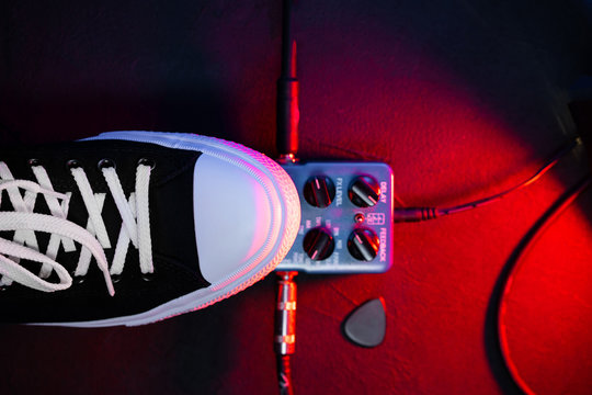 Close up of guitar player foot pressing pedal. Musician uses music effect loop machine. Man in trendy sneakers, his foot playing at stage during concert. Macro view