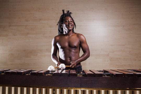 rastafarian man plays the marimba
