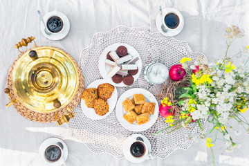 Top view of a table laid with samovar, coffee cups, sweets