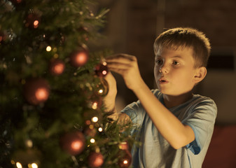 Cheerful boy decorating his Christmas tree at home