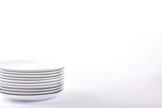 Stacked white plates on white background