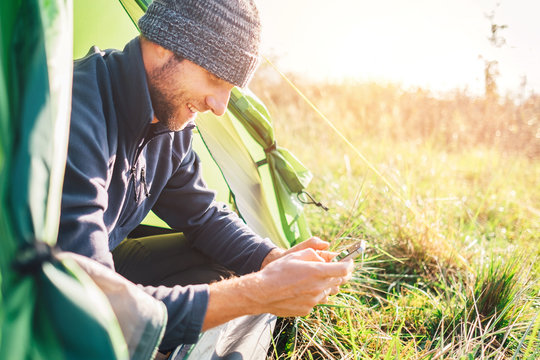 Man traveler portrait using his mobile phone and sitting in camping tent in wild nature