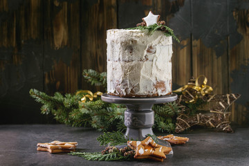 Christmas homemade white naked cake decorated by star cookie and green thuja branches on cake stand with fir tree, cookies and xmas decoration above on black table. Dark rustic style.
