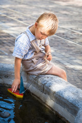 Child and his Toy Boat / Nostalgic scene: cute little boy sitting at the edge of small stony water basin and playing with his colorful wooden toy boat