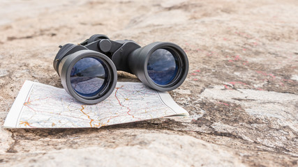 the binoculars on the old map orienteering Hiking direction stone background
