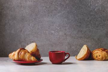 Fresh baked whole and sliced croissant with red cup of coffee espresso on white marble table with grey wall at background. Caffe breakfast