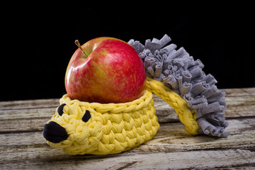 Knitted souvenir. A knitted hedgehog with red apple on white old wood background