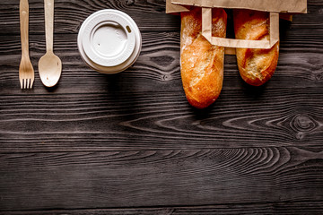 cup coffee and bread in paper bag on wooden background