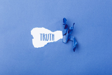 Truth word behind ripped piece of paper