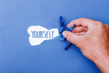 Yourself word behind ripped piece of paper