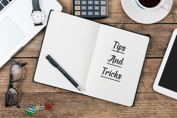 Tips and tricks message in note pad on office flat lay
