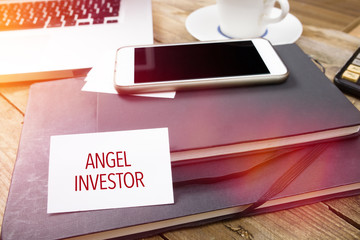 Angel Investor on business card in office setting