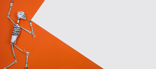 Creative and minimal Halloween layout. Skeleton on orange and white paper background. Flat lay top view. Copy space.