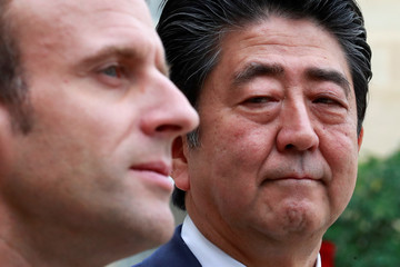French President Emmanuel Macron stands with Japanese Prime Minister Shinzo Abe in the courtyard of the Elysee Palace in Paris