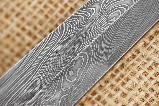 Traditional handmade Finnish knife with the abstract wave pattern of damascus steel over an old sack background.