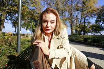 Slim young woman on bench and autumn time.