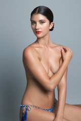 Topless young woman wearing a bikini bottom and red lipstick, portrait.