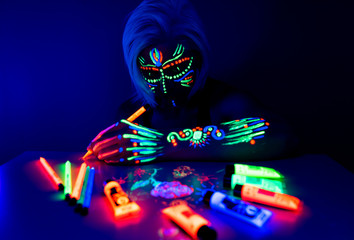 Portrait of woman with ethnic pattern, neon makeup in ultraviolet light. Fluorescent paint and pencil are on the table. Body Art design of female posing in UV, painted face, colourful make up