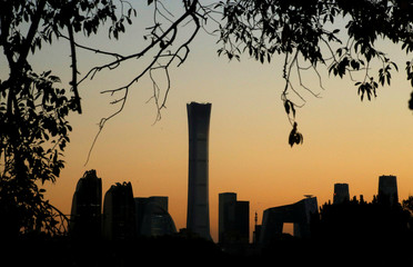 The cityscape of the Beijing Central Business District is silhouetted against the sky during sunset