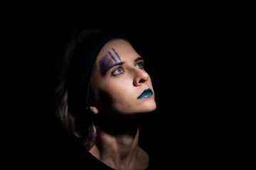 Close-up portrait of young beautiful woman with face art on dark background with copy space. Art concept