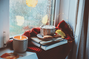 cozy autumn morning at home. Hot cocoa with marshmallows and candle on window in rainy cold day. Spending holidays at home.