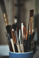 Stylized photo of paint brushes in a glass