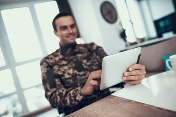 Smiling Military Man Uses Tablet in Living Room