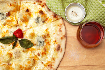 Pizza on wooden table with pepper and glass with wine