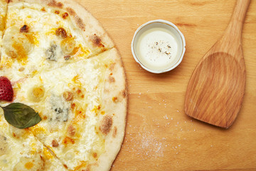 Pizza on wooden table with pepper