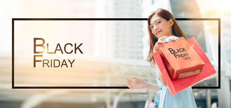 Happy asian woman with red shopping bag celebrating Black Friday on the mall.Stylish girls visiting Black Friday sale.Young woman holding black friday shopping bag in the city.