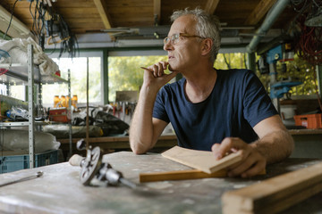 Mature man at workbench in his workshop thinking