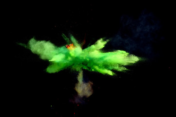 Colorful explosions of powder paint and flour combined  together explode in front of a black background to give off fantastic  multi colored cloud forms.