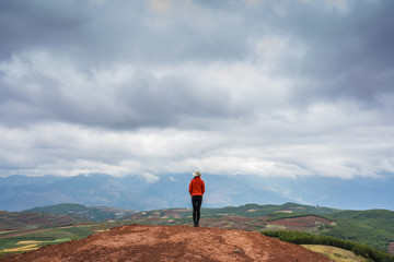 China, Yunnan province, Dongchuan, Red Land, young woman standing on viewpoint