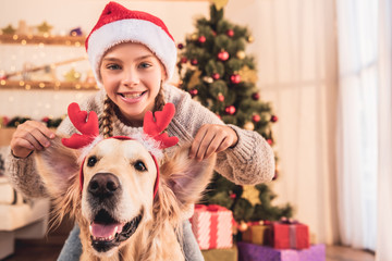 smiling kid in santa hat and golden retriever dog with deer horns having fun at home near christmas tree