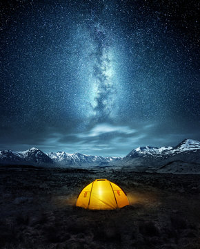 Camping in the wilderness. A pitched tent under the glowing  night sky stars of the milky way with snowy mountains in the background. Nature landscape photo composite.