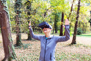 Senior Woman Fun With Virtual Reality Headset In Forest