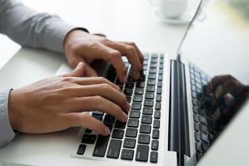 Crop shot of man typing on laptop keyboard working at table in daylight